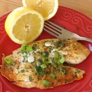 Baked lemon pepper tilapia on plate with a lemon half and fork