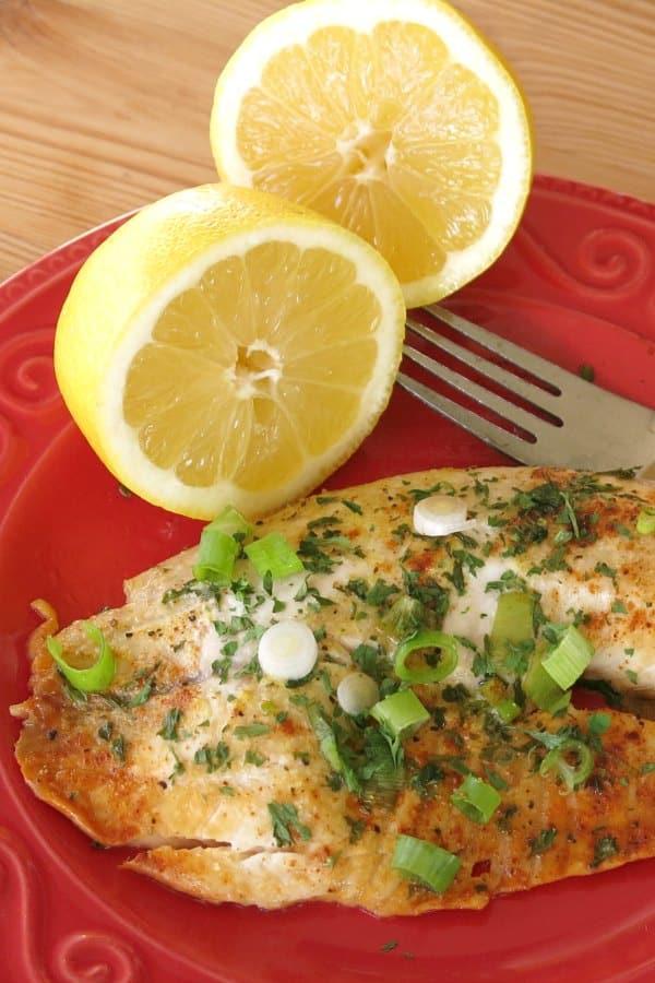 Baked Lemon Pepper Tilapia on dish with lemon halves and fork