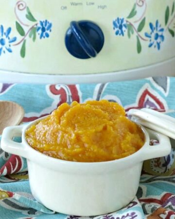 Crock-pot butternut squash in a bowl in front of a slow cooker