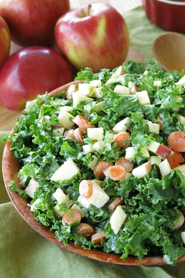 Easy Kale Apple Slaw mounded in bowl with apples next to it