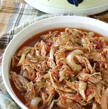 Healthy Salsa Chicken in serving dish with crock-pot in the background