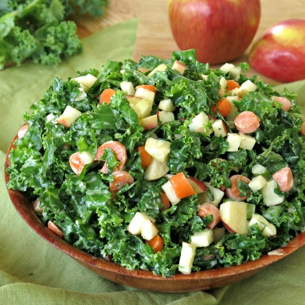 Kale apple slaw in bowl with apples in the background