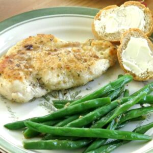Pan Fried Lemon Chicken Cutlets drizzled with lemon sauce on plate with green beans