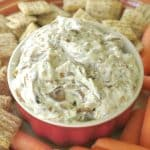 Caramelized Onion Dip with Greek Yogurt in bowl surrounded by carrots and crackers