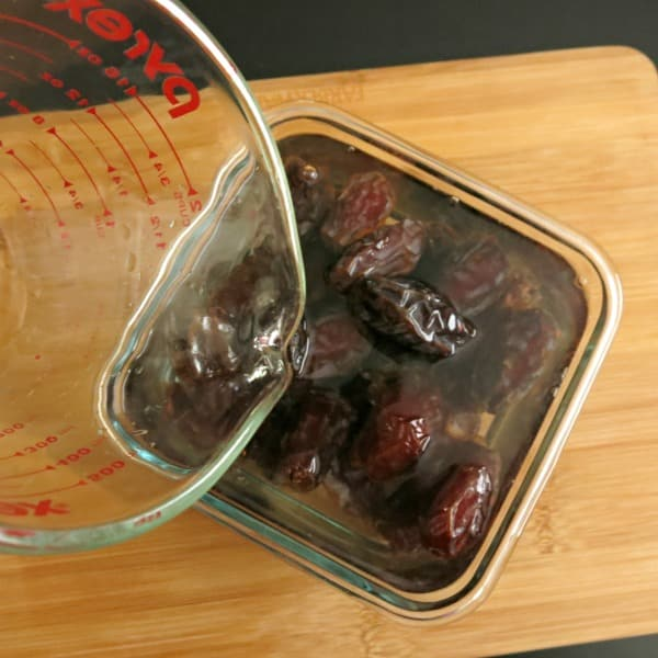 Water pouring over Medjool dates in a glass container