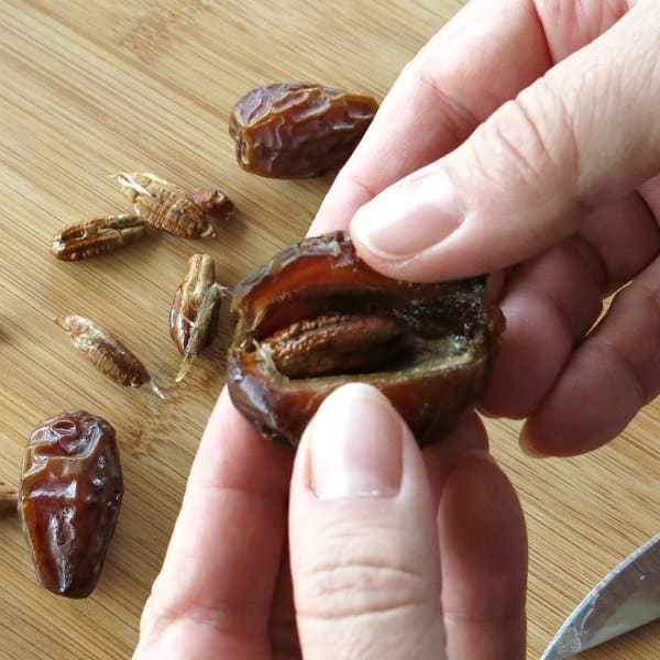 Fingers pulling the slit of a medjool date apart to expose the pit.