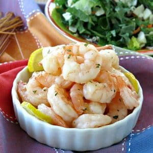 Skillet shrimp piled in a bowl with salad and pasta in the background.