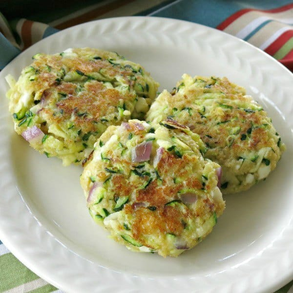 3 zucchini fritters with feta cheese and red onion on a plate
