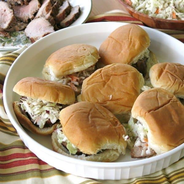 Pork Tenderloin sliders topped with coleslaw on a serving platter