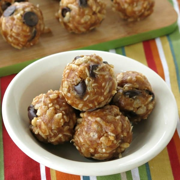No-bake date balls with rice krispies in a bowl with more on a cutting board in the background.