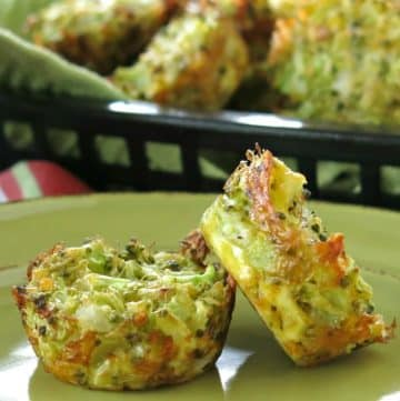 Two broccoli muffins on plate with a basket of muffins behind them.