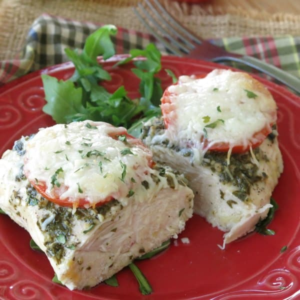 Healthy Pesto Chicken on plate cut into two pieces with fork in background.