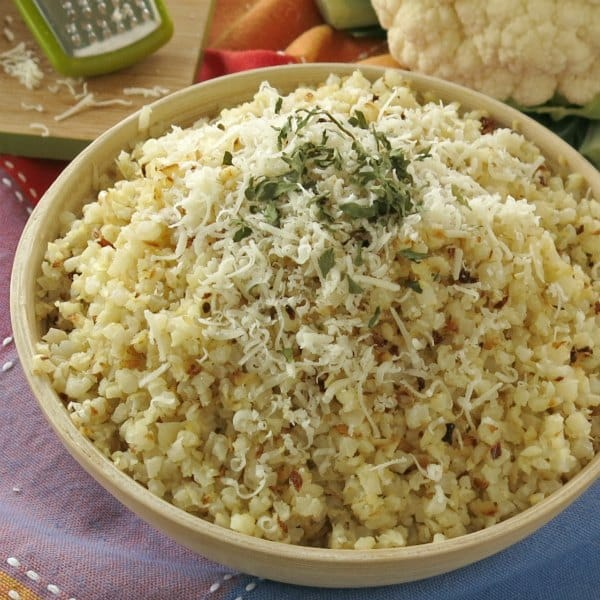 Bowl full of roasted cauliflower rice topped with parmesan cheese and parsley
