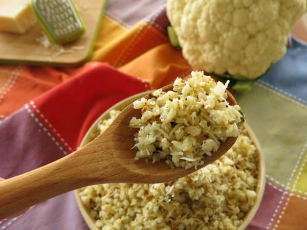 Roasted Garlic Parmesan Cauliflower Rice on wooden serving spoon over bowl.