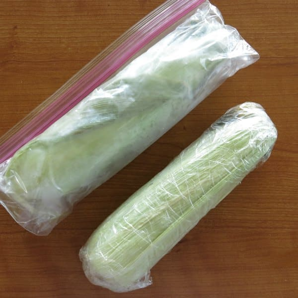 Two cobs of corn: one wrapped in plastic and the other in a plastic bag, ready to go into the freezer.