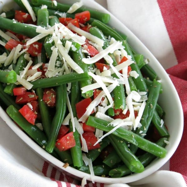 Easy green beans and tomatoes topped with Parmesan Cheese in a serving dish.