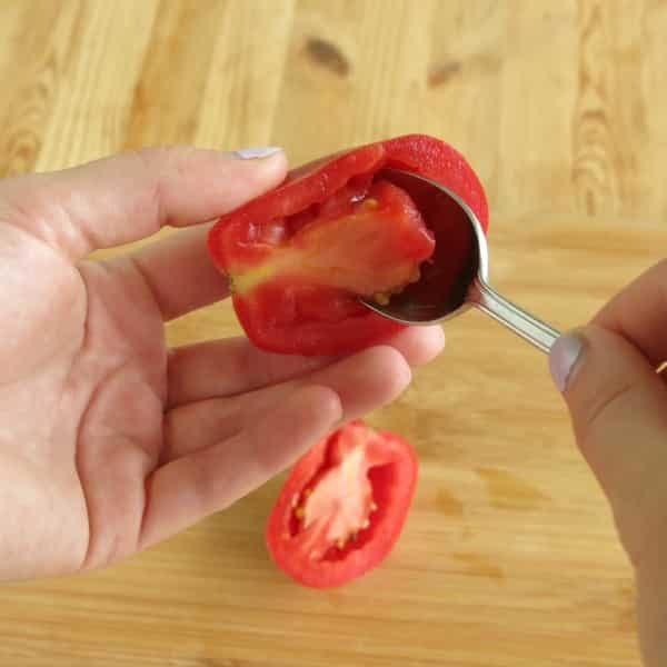 Spoon removing flesh from the center of half a Roma tomato