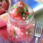 Watermelon Basil Feta Salad in a mason jar with a fork next to it.