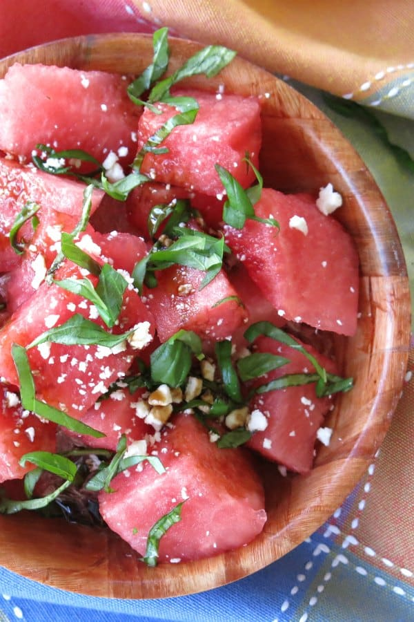 Watermelon Salad with basil, feta cheese and balsamic glaze in a bowl.
