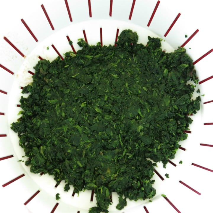Chopped spinach pressed into the bottom of strainer