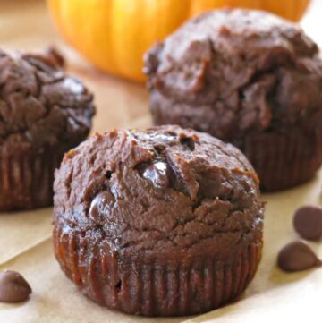 Close-up of healthy chocolate pumpkin muffin with 2 muffins and pumpkin in the background.