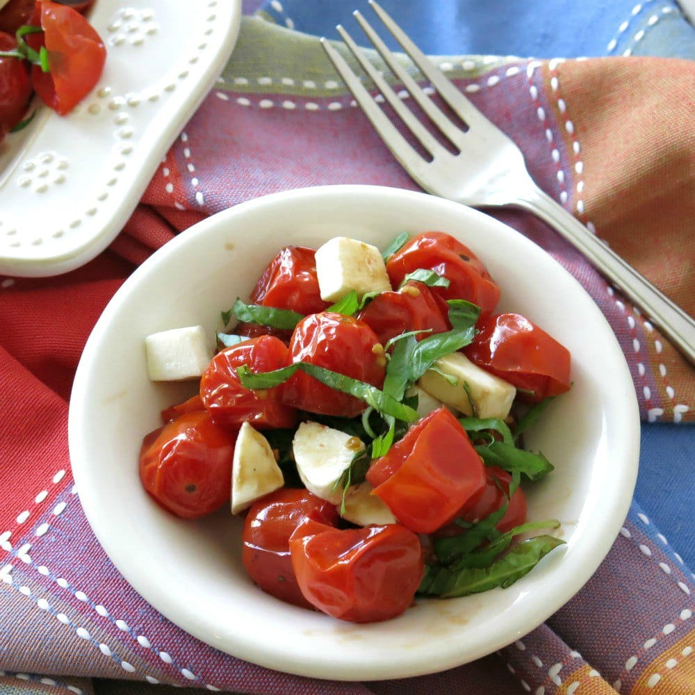 Grape tomato Salad in a small bowl with a fork next to it.