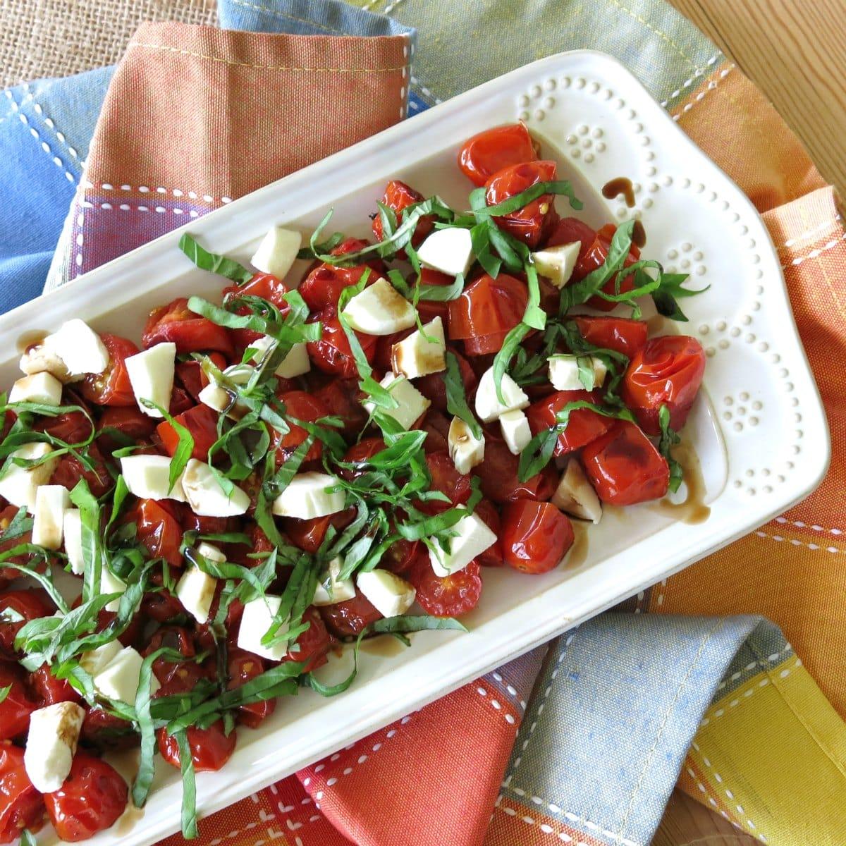 Roasted Grape Tomato Caprese Salad on a rectangular plate