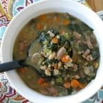 Ladle lifting white bean, sausage and spinach soup from bowl