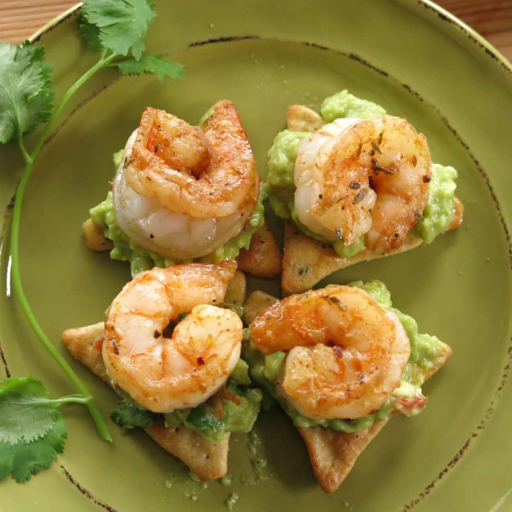 4 pieces of shrimp and guacamole appetizer on plate.