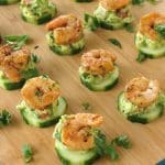 Cajun Shrimp Guacamole Bites on Cucumber rounds on serving board.