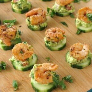 Cajun Shrimp Guacamole Bites on Cucumber rounds on serving board.