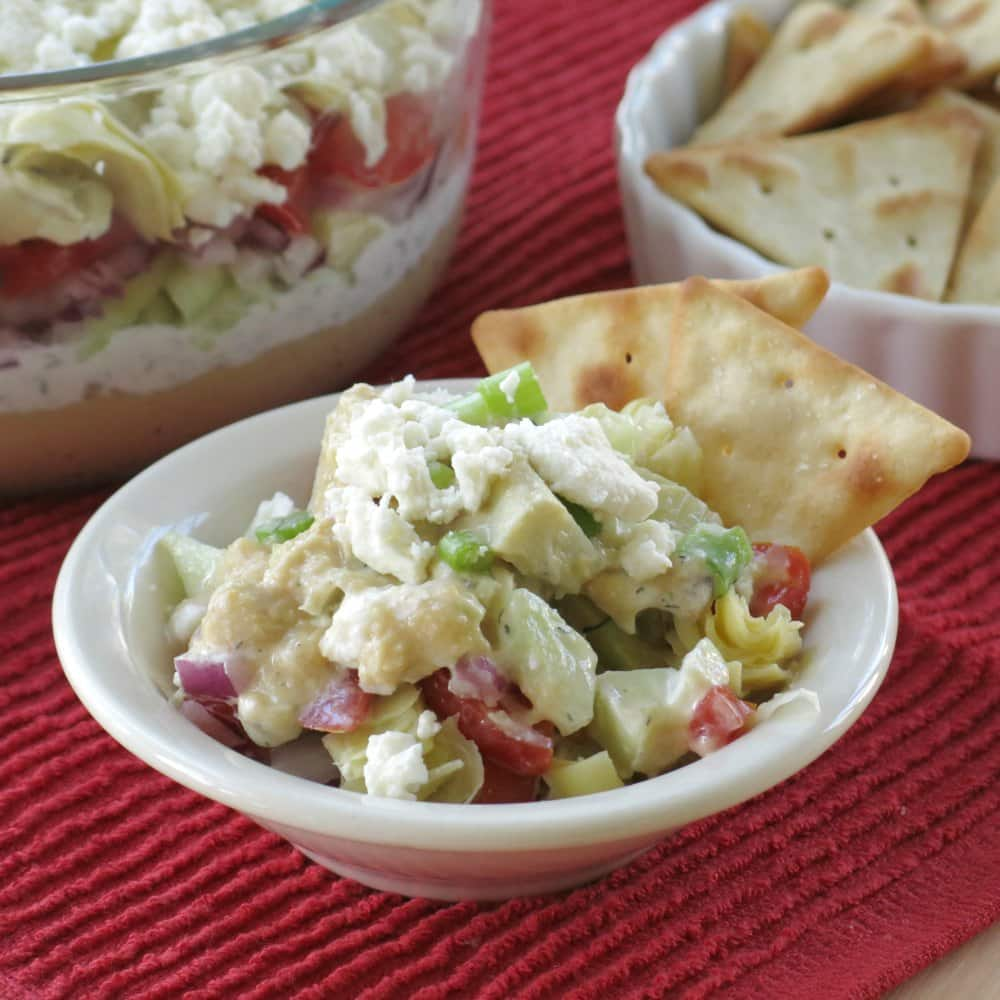 Serving of Greek dip in a small bowl with two crackers on the side.
