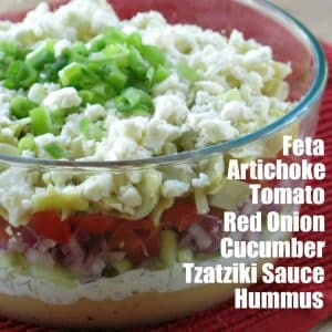 Greek Layer Dip in glass bowl with layers labeled.