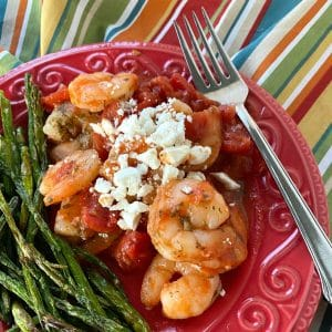 Serving of Greek shrimp with tomatoes and feta cheese on plate next to asparagus.