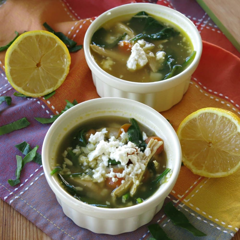 Two bowls of lemon chicken soup with cauliflower and feta cheese.