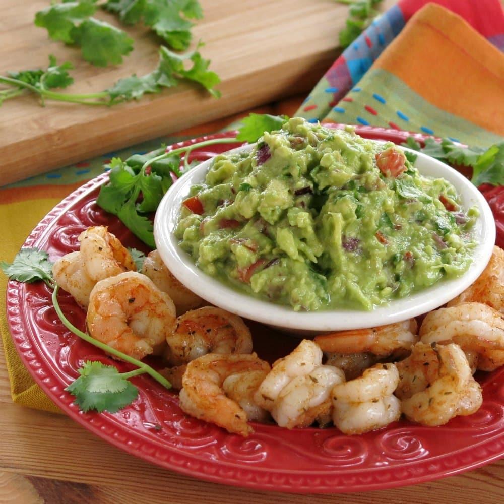 Guacamole surrounded by blackened shrimp.