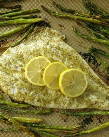 Cooked Turbot Fillet with mustard dill sauce and lemons on a baking sheet surrounded by asparagus