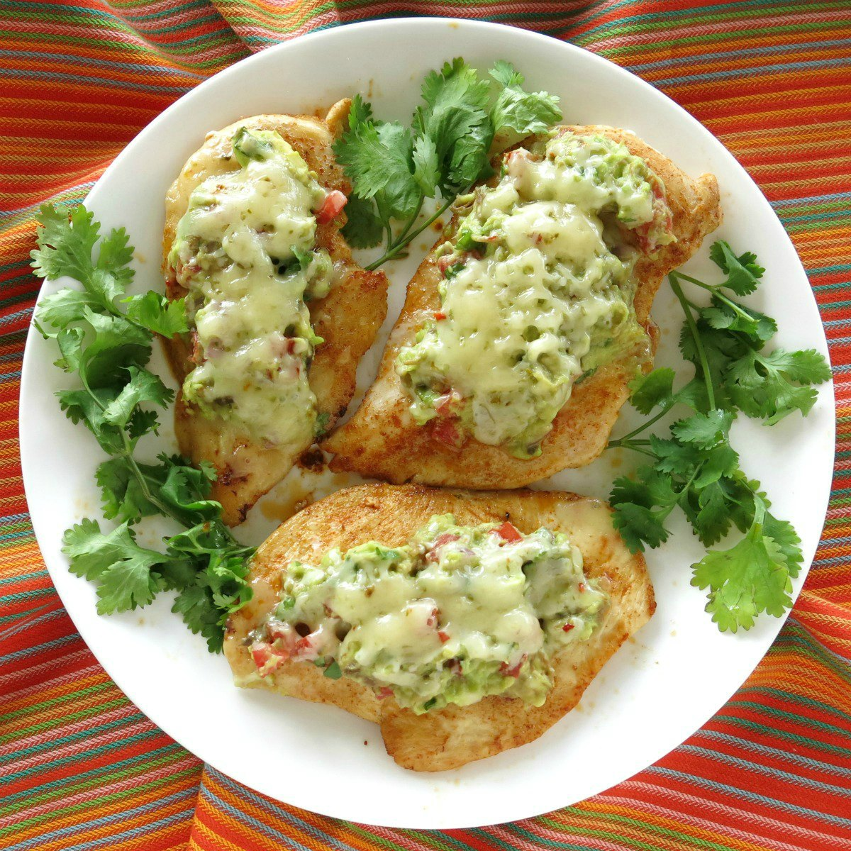 Guacamole chicken melts on a plate surrounded by cilantro