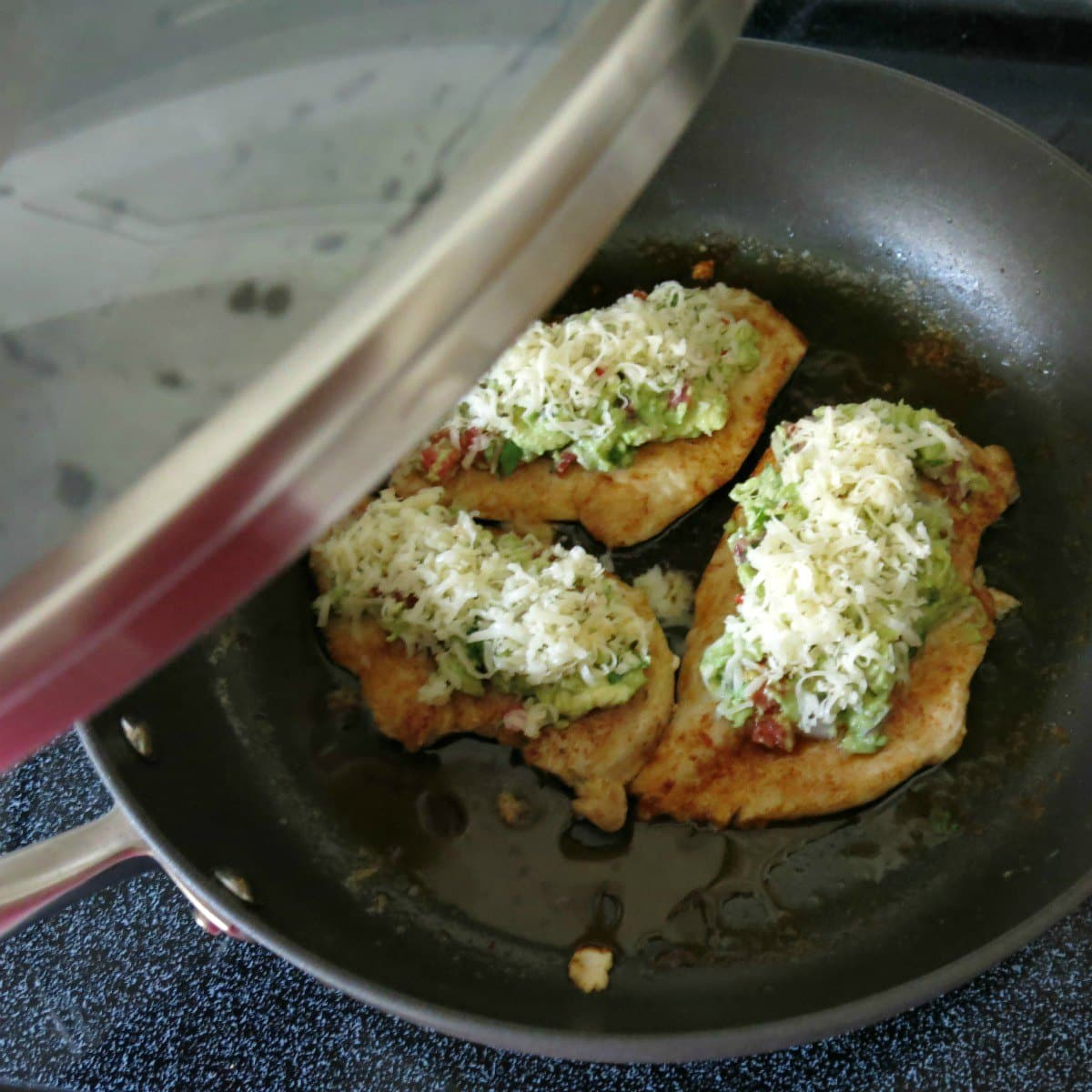 Chicken guacamole in pan before cheese has melted with lid being placed on top
