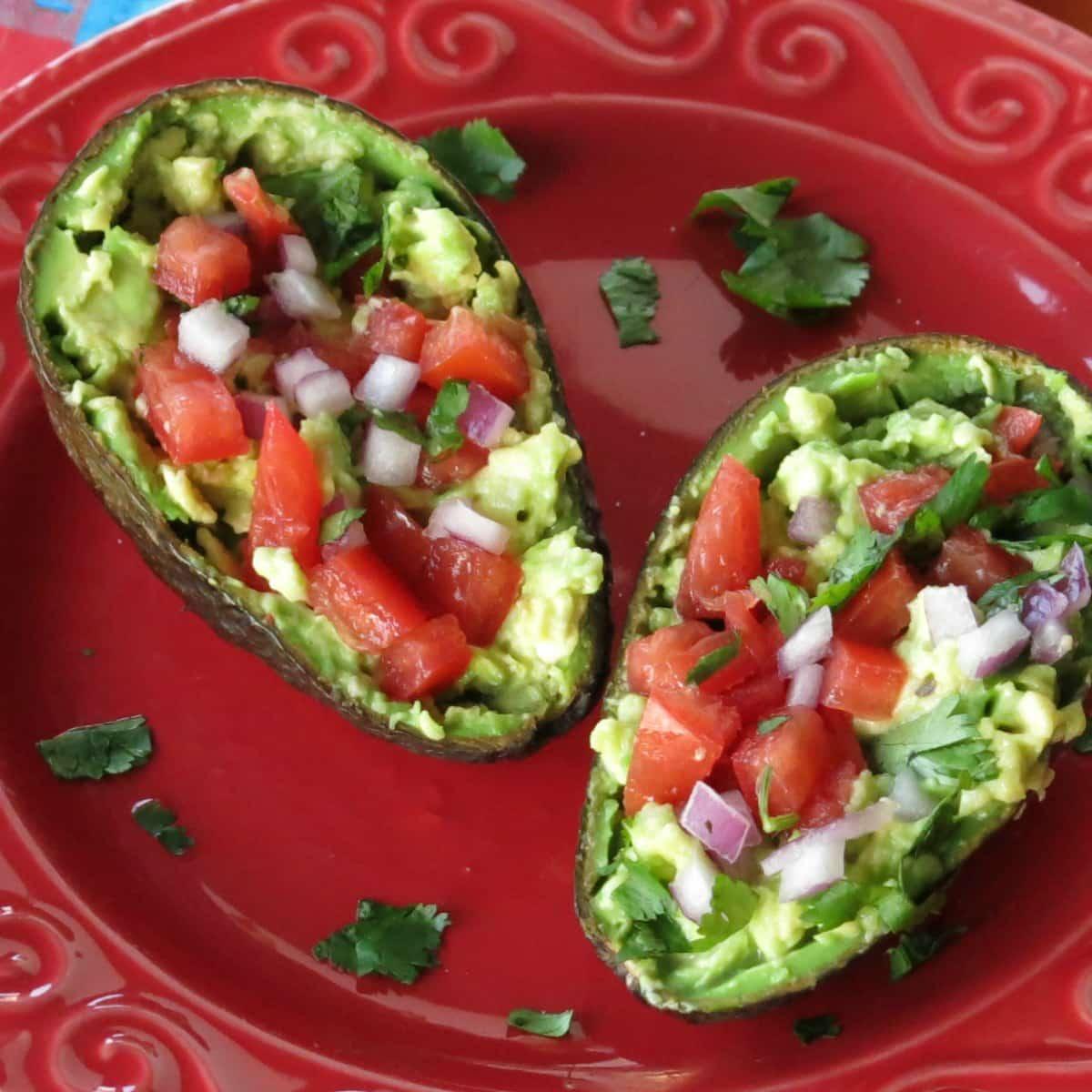 An avocado cut in half with guacamole inside each half