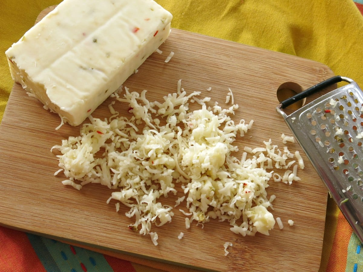 Block of Pepper Jack cheese on cutting board with shredded cheese and grater