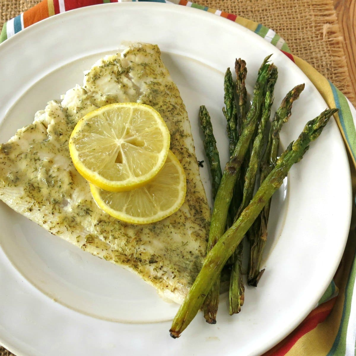 Serving of roasted Turbot with lemon slices on top and asparagus on plate.