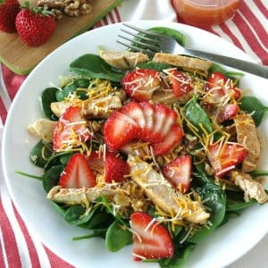 Spinach Strawberry Walnut Salad topped with chicken on a plate with walnuts and dressing in the background.