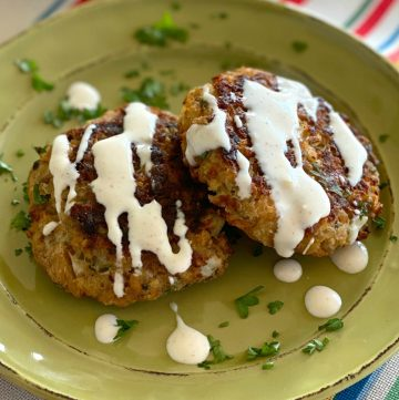 Two baked salmon cakes on a plate.