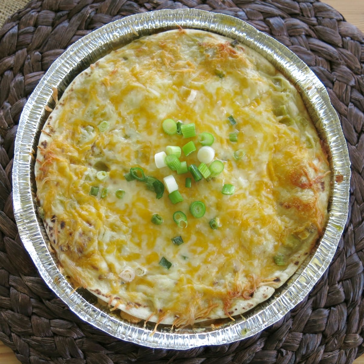 Cooked chicken enchilada pie in a round pan.