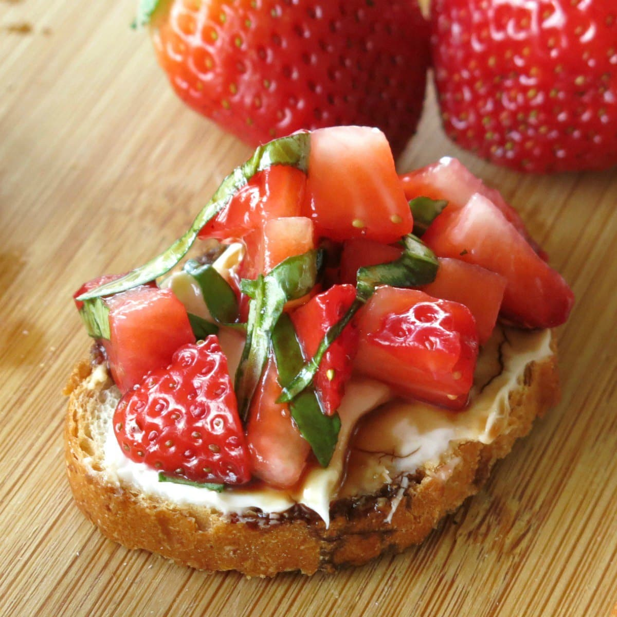 Strawberry Bruschetta with cream cheese, basil and balsamic vinegar reduction on thin slice of baguette.