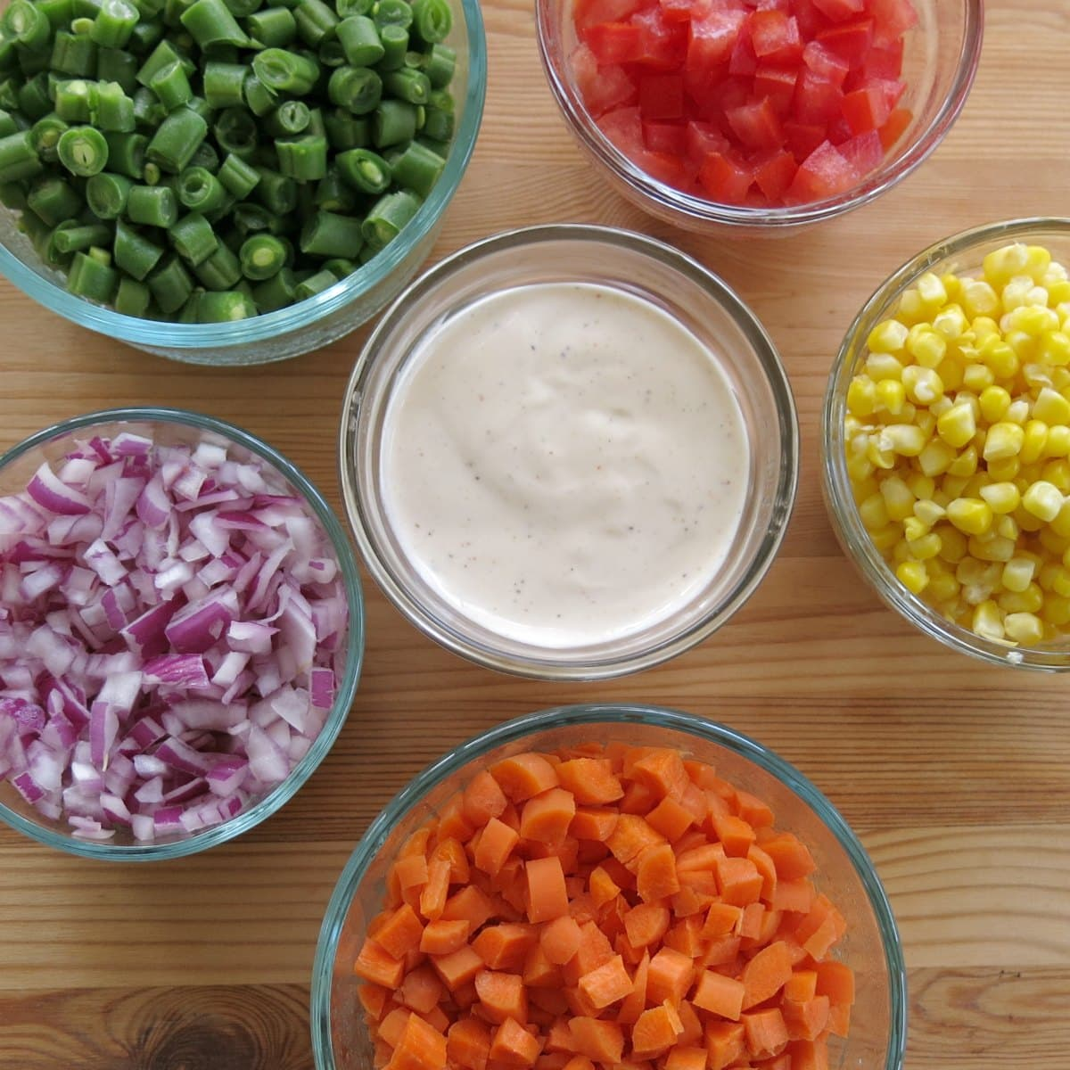 Small bowls with finely chopped vegetables surrounding a bowl of ranch dressing.