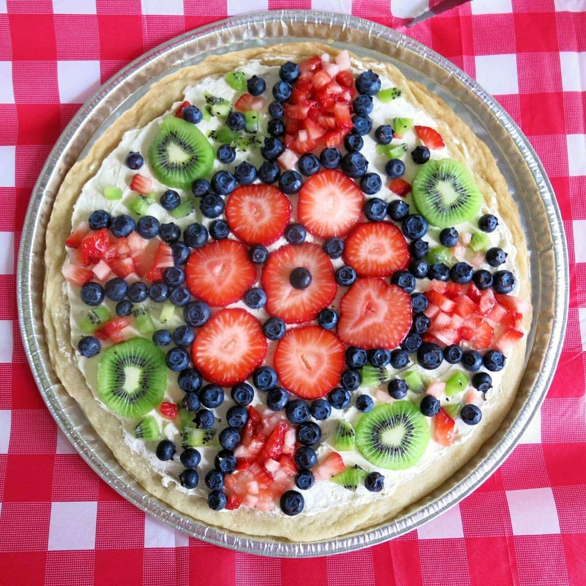 Color pizza cookie topped with kiwi, strawberries and blueberries.