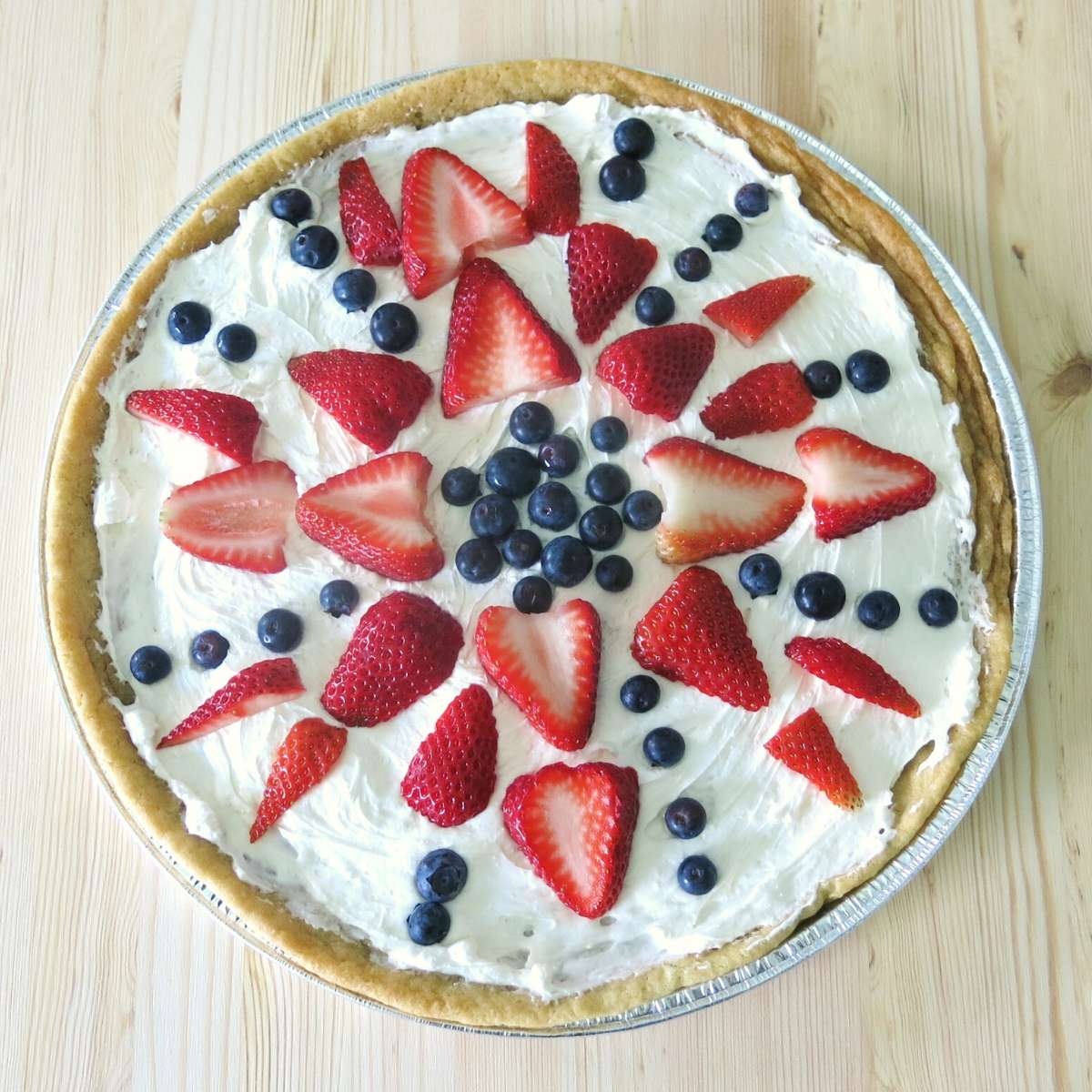 Fruit pizza cookie decorated with strawberries and blueberries.