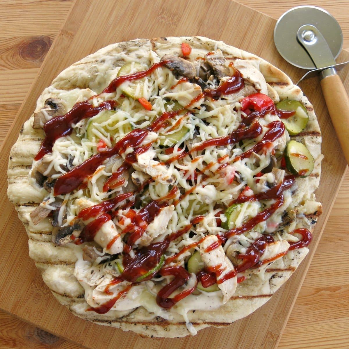 Finished BBQ Chicken Pizza on cutting board with a pizza cutter.
